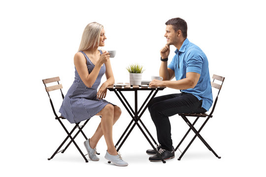 Young woman and a young man seated at a coffee table