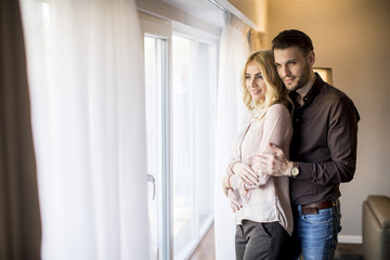 Young couple standing by the window in the room