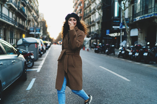 Happy international student girl crossing the road while going to the party dedicated to the new study year in the university. Smiling hipster girl in stylish clothes going to visit her friends