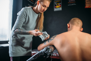 Tattoo master sprays the freezing on clients skin