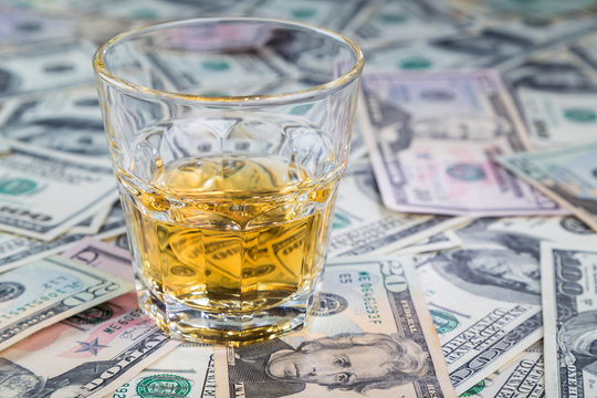 glass of whiskey is on dollar bills of different denominations