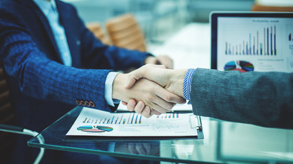 handshake financial partners on the background of the workplace with financial papers