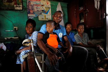 Amputee football player Emmanuel Ibeawuchi sits with his family at his residence in the Aguda district in Lagos