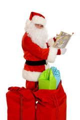Santa Claus holding map, sacks of presents on the ground