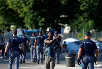 Italian police identify migrants in a camp set by the Baobab aid group in Rome