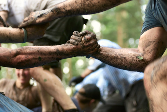 Folks help each over in a mud race with obstacle course. In a motion.