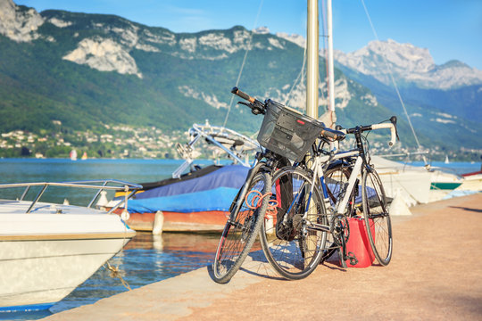 .Two bicycles on the pier on the background of the lake and mountains in the French city of Annecy. Upper Savoy. France.