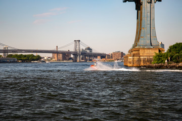 New York, City / USA - JUL 10 2018: Man wearing clown suite riding jet ski water bike in East River under Manhattan Bridge