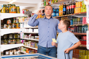 Male with phone and son in food shop