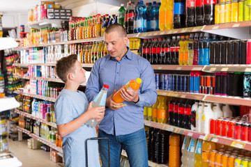 Father and son in store looking for mineral drinks