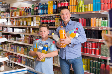 Cheerful father and son with purchases in store