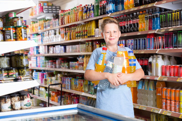 Portrait of happy preteen boy with purchases in supermarket