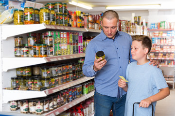 Father and boy choosing goods with shopping list in grocery store