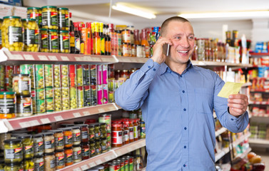 Father with son choosing food, advising on phone
