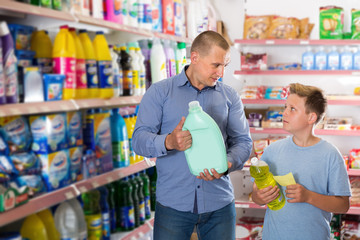 Father and son looking household cleaners in supermarket
