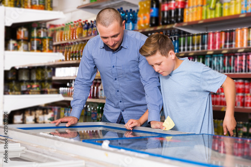 father doing shopping with boy looking at shopping list stock photo
