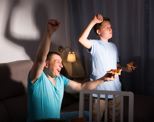 Smiling man is watching TV and cheering for football team with his son