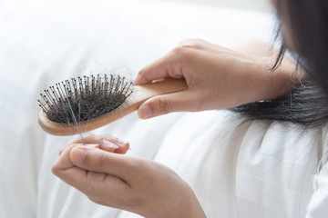 woman looking at her hair for hair loss problem Fotobehang
