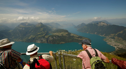 People stand on a lookout above Lake Lucerne on Mount Fronalpstock, near Stoos