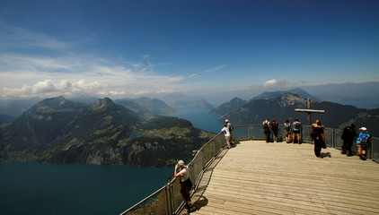 People stand on a lookout above Lake Lucerne on Mount Fronalpstock near Stoos