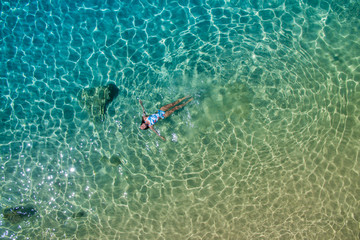 Relaxed female swimming in beautiful sea water
