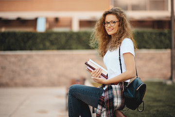 Female student sitting in a campus and waiting for class to begin. Books in hands.