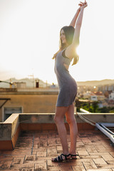 Gorgeous young woman standing on roof