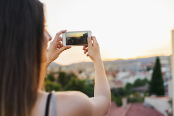 Female taking picture of town at sunset