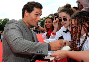 "Cast member Henry Cavill signs autographs as he arrives for a photocall for the world premiere of the film ""Mission: Impossible - Fallout"" in Paris"