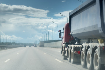 Tipping lorry driving on the asphalt road in the rural landscape. sky with clouds