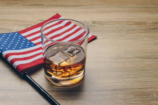 close up of a glass of bourbon whiskey and the flag of the United States of America on wooden table