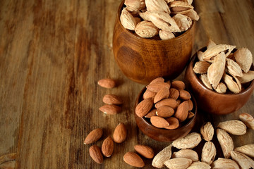 Peeled and unpeeled almond nuts in wooden bowls