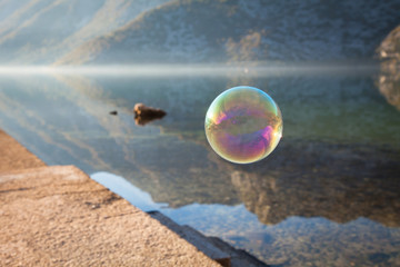 Rainbow soap bubble on background of sea, mountains at sunset. Bubbles fly above water with reflection.