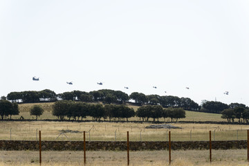 A few Eurocopter Super Puma helicopters flying in line over a farm