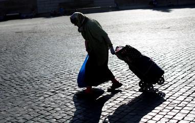 A woman walks in the Popolo's Square in Rome