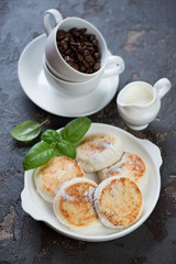 Curd fritters with coffee for breakfast, vertical shot on a brown stone background, selective focus