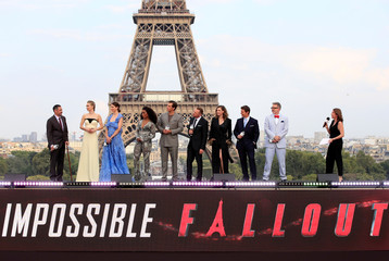 """Director Christopher McQuarrie and cast members pose in front the Eiffel Tower during the world premiere of the film """"Mission: Impossible - Fallout"""" in Paris"""
