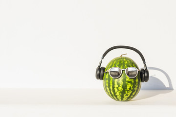Creative and summer photography of watermelon in the form of a human head with glasses and headphones against a white wall background. Concept