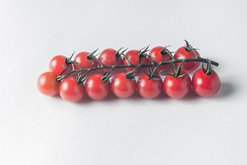 branch of fresh tomatoes cherry on a white background