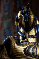 Statue of Anubis with the mummy of the deceased on a black background