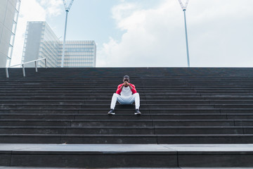 Ethnic male resting on stairs after workout