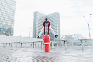 Sporty African-American man practicing parkour in city