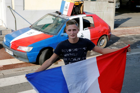 Florentin Drubay, a French soccer fan, poses with a French flag in front of his  customized blue, white and red car, several days before Soccer World Cup final, in Lieu-Saint-Amand