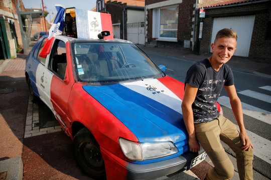 Florentin Drubay, a French soccer fan, poses in front of his customized blue, white and red car, several days before Soccer World Cup final, in Lieu-Saint-Amand