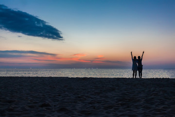 Young two girls having fun on the beach against a backdrop of a sunset over the sea. Phuket, Thailand