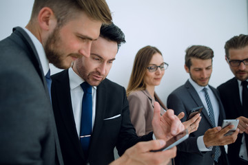 business team looking at the screens of their smartphones