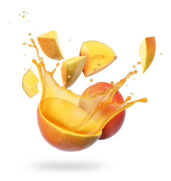 Mango broken into pieces with splashes of juice on white background