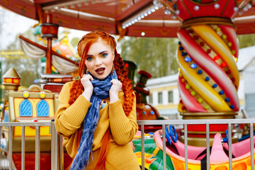 young cheerful red-haired girl posing on the background of the carousel in the amusement Park. Portrait of a woman with bright makeup and long red hair braided in braids. She poses, has fun and plays.