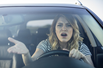 Angry woman driving a car. Wall mural