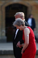 British Prime Minister Theresa May and U.S. President Donald Trump walk across the courtyard at Blenheim Palace near Oxford